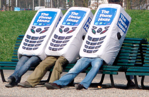 Three people on a bench dressed up as cell phones.